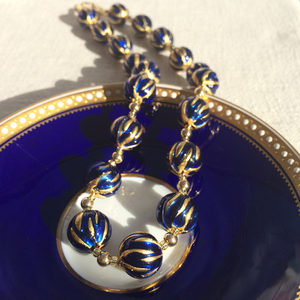Necklace with dark blue (cobalt) appliqué over gold Murano glass sphere beads on gold