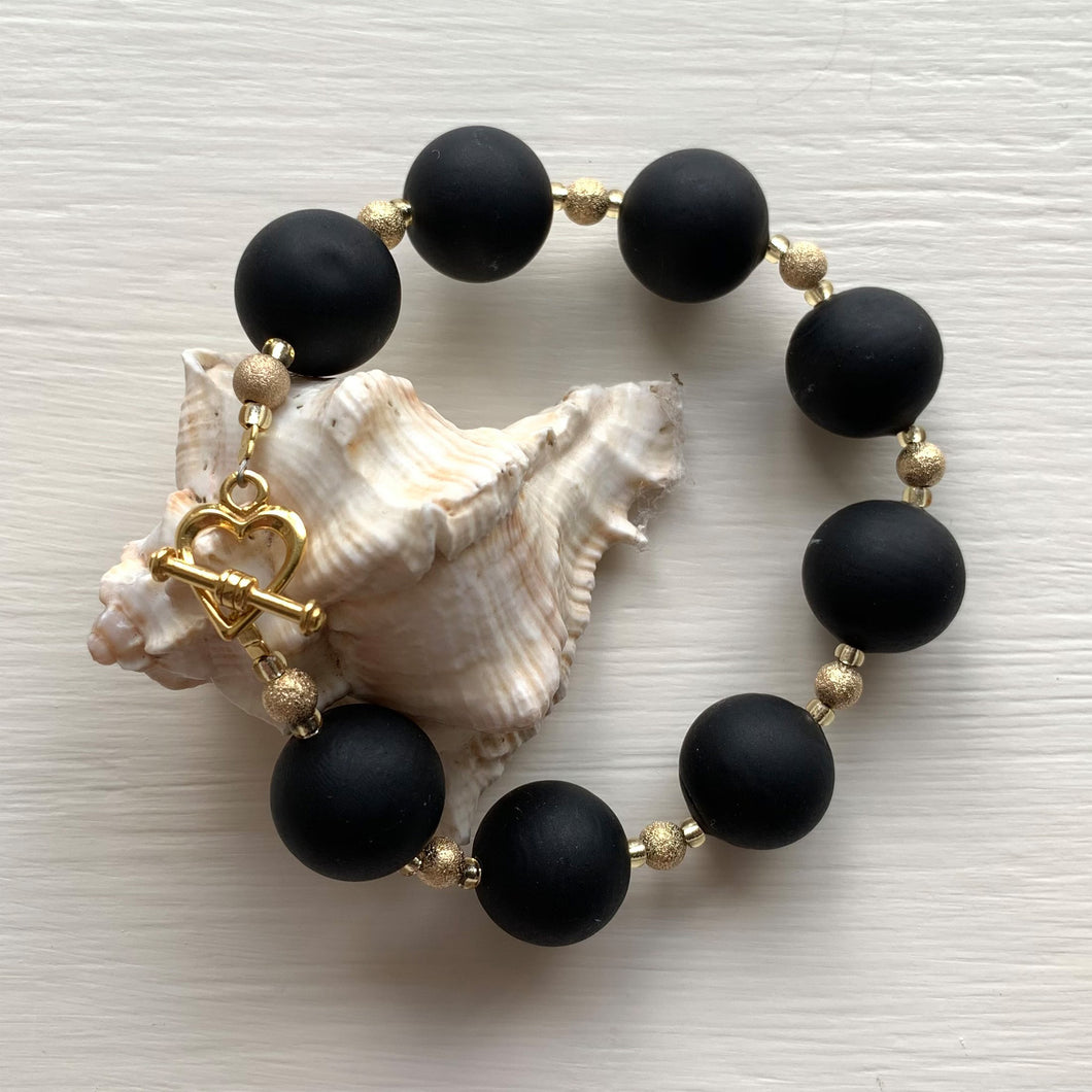 Bracelet with matt black Murano glass small sphere beads on gold stardust beads and clasp