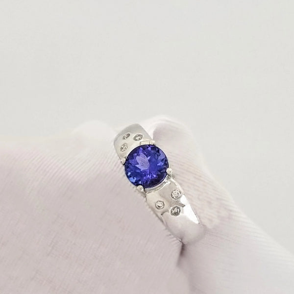 Three Diamonds on Each Side decorating a Round Tanzanite set in a Ring