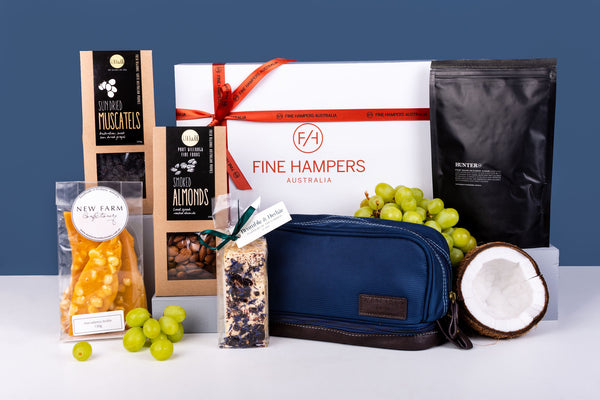 White hamper box with products standing in front of it with blue background and fruit to present