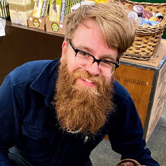A smiling man with glasses, sandy blonde hair, and a glorious reddish beard.