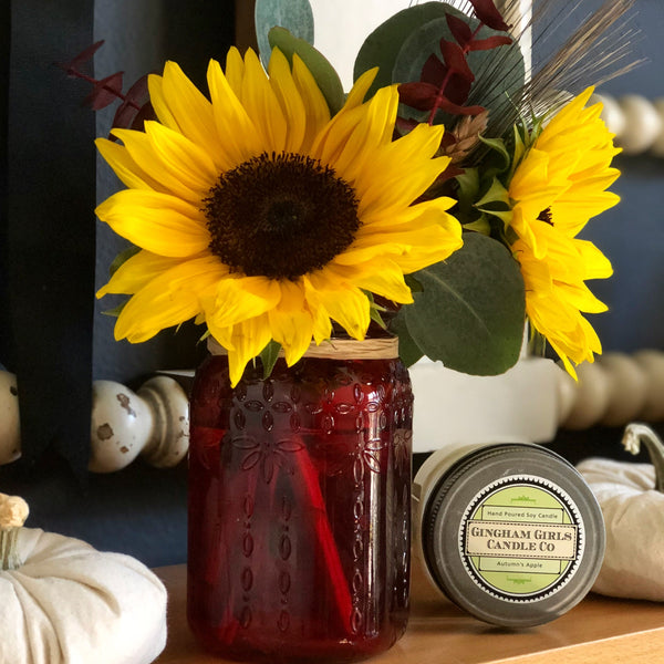 Homemade apple soy candle placed next to daisies