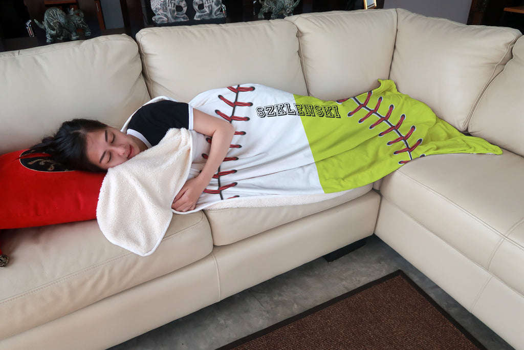 Girl lying on sofa wearing softball beach blanket