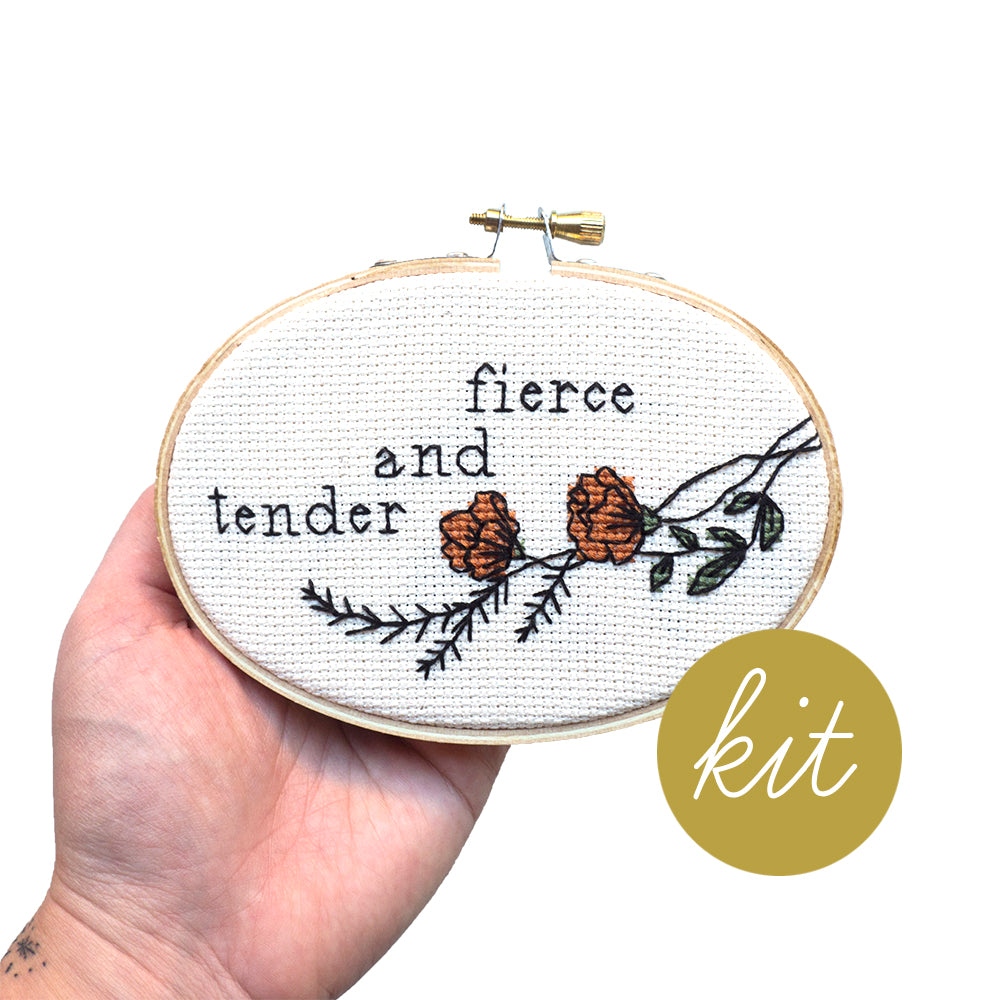 orange flowers with green leaves and black outline, text reads fierce and tender, DIY cross stitch kit