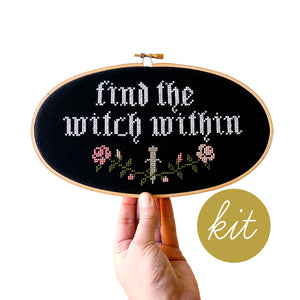 gothic font reads Find the Witch Within in white on black aida cloth, pink flowers with green vines wrapping around sword, DIY cross stitch kit