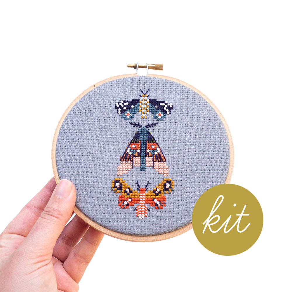 three very colorful moths on blue aida cloth, DIY cross stitch kit
