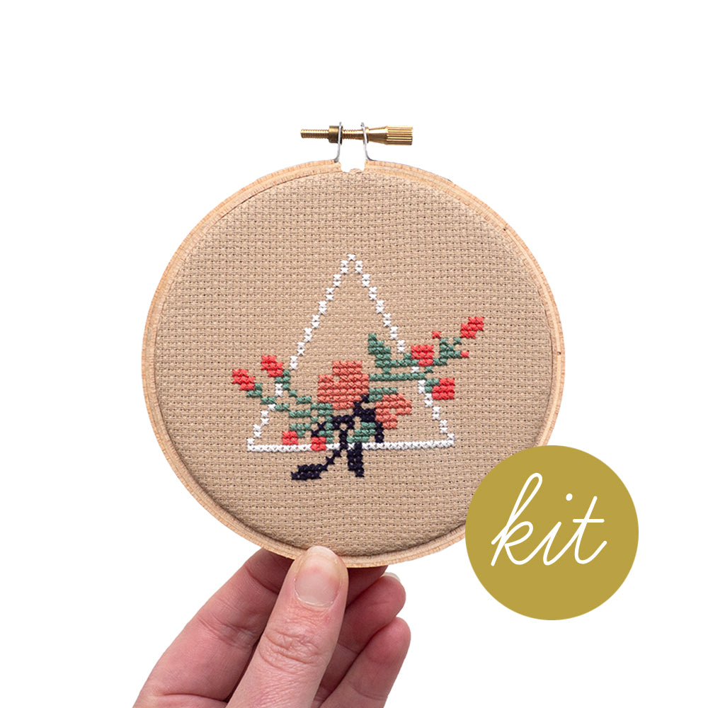 two tone pink flowers with green leaves and white pyramid shape behind on natural aida cloth, DIY cross stitch kit