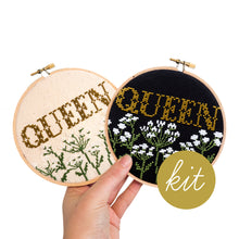 Load image into Gallery viewer, traditional cross stitch letters reading Queen in gold with queen anne's lace flowers in white and green underneath, stitched on black and cream aida, DIY cross stitch kit