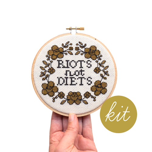 gold flowers outlined with black thread and text reading Riots not Diets in black, DIY cross stitch kit