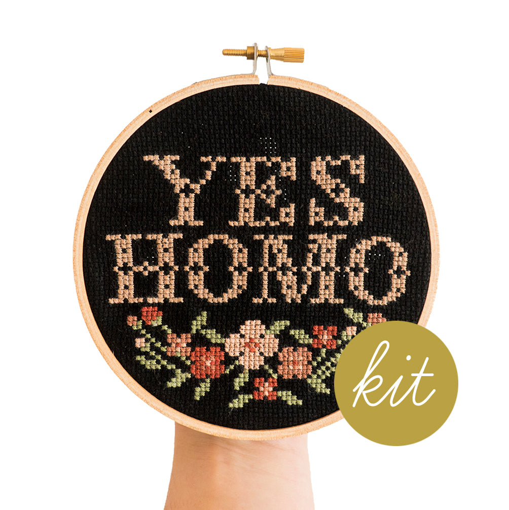 traditional cross stitch font reads Yes Homo in pink with multiple color pink flowers stitched on black aida cloth, DIY cross stitch kit