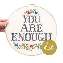 Load image into Gallery viewer, large font reads You Are Enough with multiple color flowers on top and bottom of text, DIY cross stitch kit