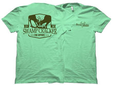 "Mint green tee shirt with two bucks locking horns on the front with the words ""Swamp Cracker Fine Apparel"" written underneath."