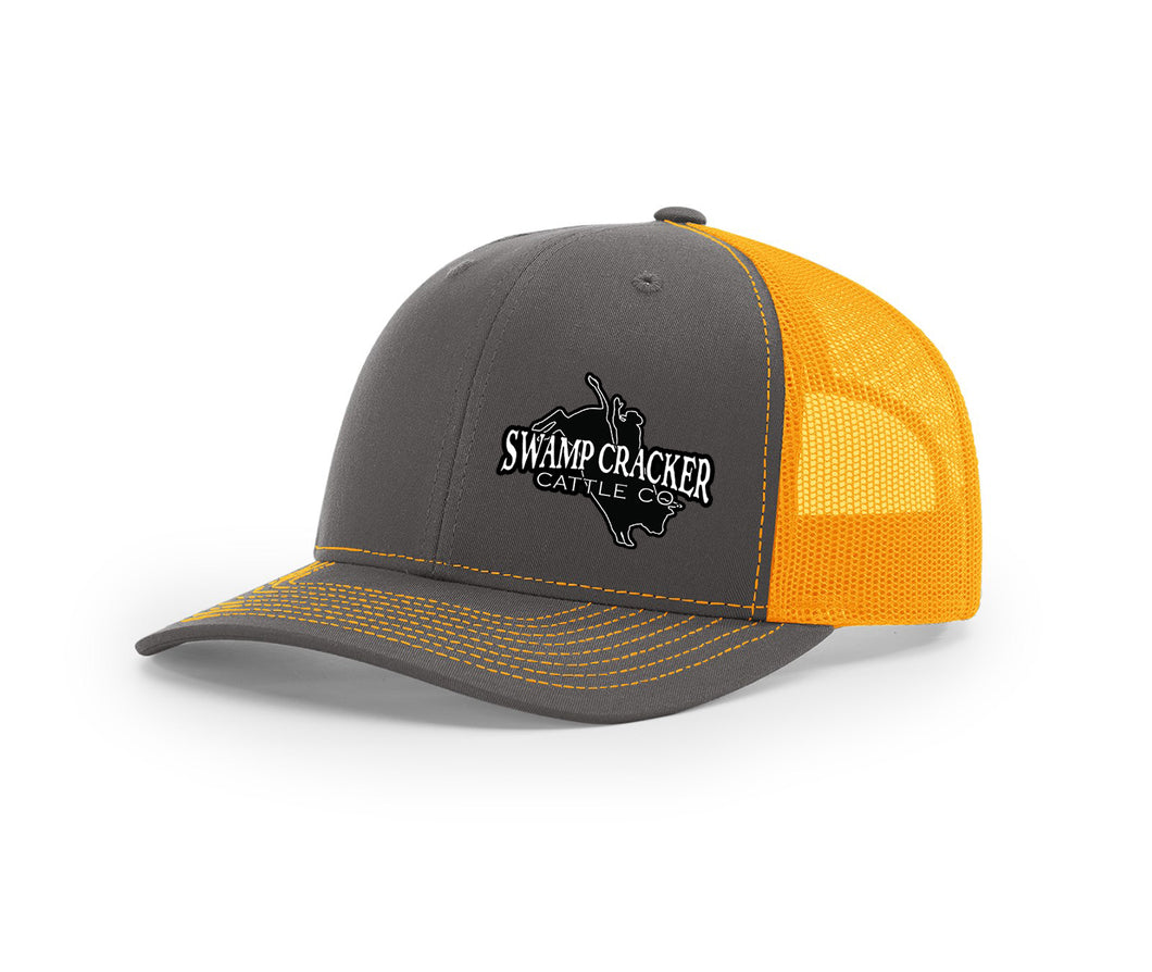 Charcoal and orange mesh trucker hat with the Cattle Co. by Swamp Cracker bull rider logo sewn on the front.
