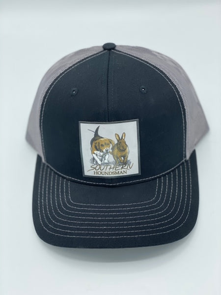Black and charcoal Southern Houndsman outdoorsman hat from Swamp Cracker Outdoor Apparel with a beagle chasing a rabbit patched on the front.