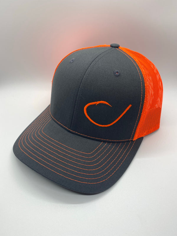 Charcoal and neon orange mesh trucker hat with a round fish hook on the front from Swamp Cracker Outdoor Apparel.