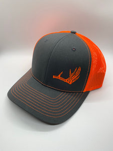 Charcoal and neon orange mesh trucker hat with a deer shed on the front from Swamp Cracker Outdoor Apparel.