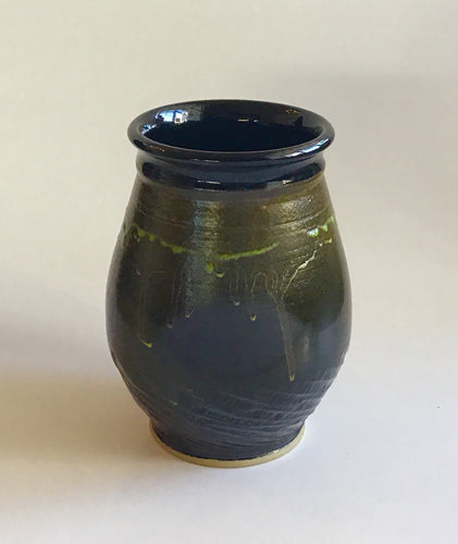 Black vase with green drip