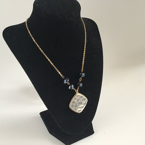 Hammered silver pendant on gold chain necklace