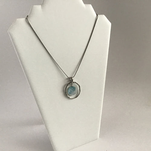 Silver necklace with ring pendant and small, pearlescent shell accent