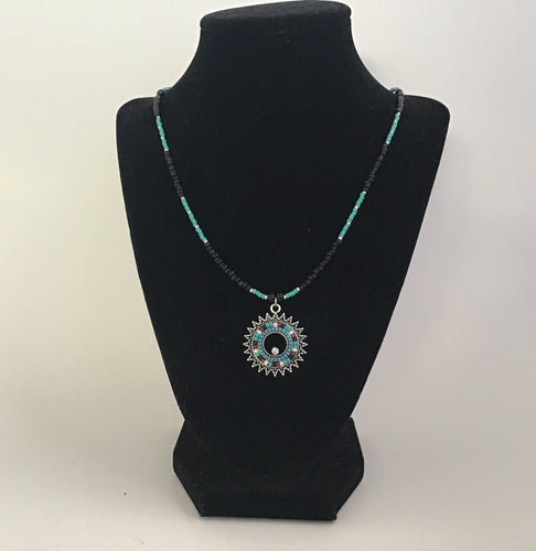 Black and teal sunburst style necklace with beaded chain