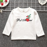 White t-shirt from baby girl clothing set made of cotton that comes with a hooded jumper, pants and t-shirt that has roses on it.