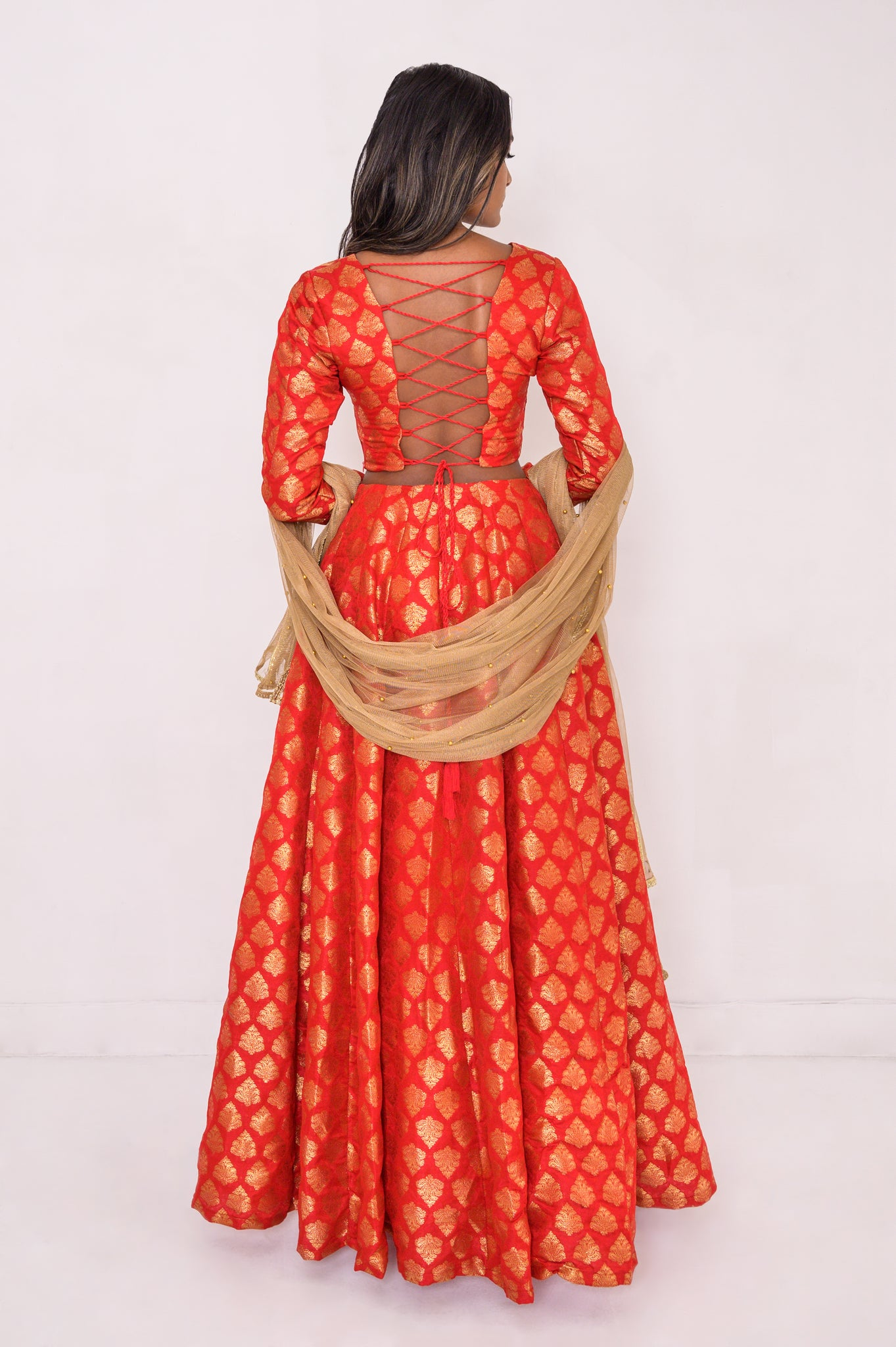 A rich red and gold jamawar lengha top and skirt. No dupatta included. (Model in Everyday Gold Dupatta)  Backless top with drawstrings and a skirt full of body and movement.  Skirt with POCKETS!