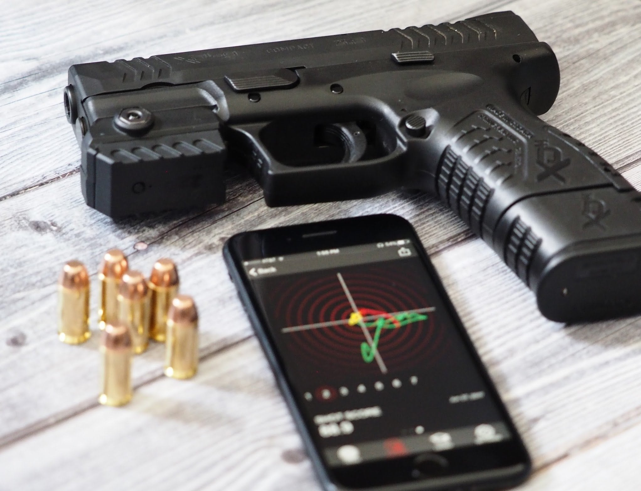 MantisX Firearm Training System - gun, smartphone and bullets