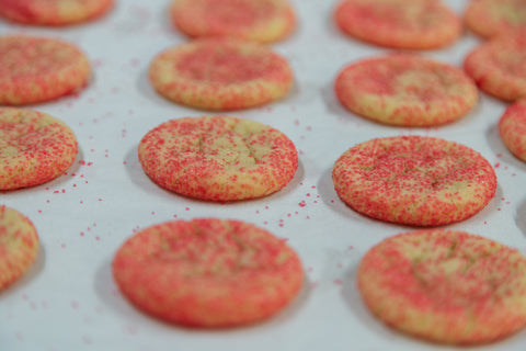 Tray of sugar cookies with red sprinkles.