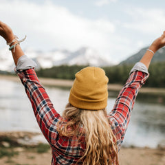 Picture of woman feeling freedom by a lake and mountains