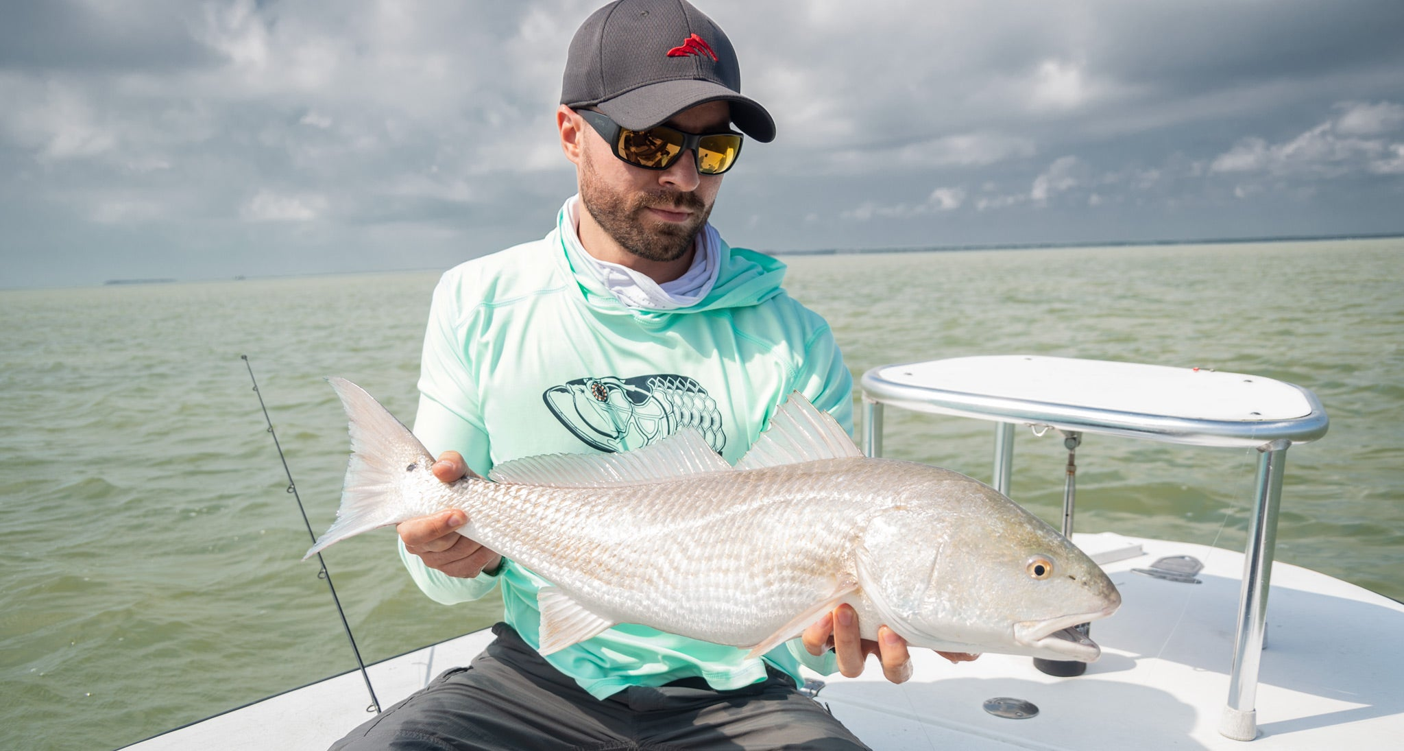 Wicked Catch holding redfish wearing Super Fly Tarpon performance fishing hoodie shirt