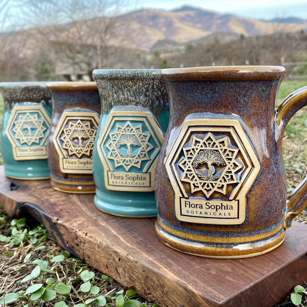 Four ceramic mugs with the Flora Sophia Botanicals logo