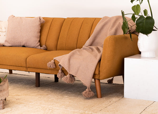 Orange sofa with pillows and a blanket on top