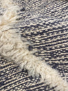 detail of kilim rug with white wool line on gray rug