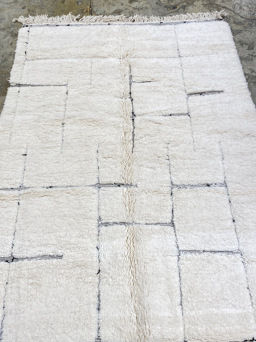 area wool rug white with geometric black lines and tassels