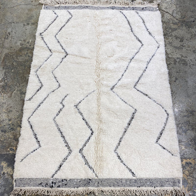 area soft wool rug off white with geometric  design black lines and tassels, authentic handmade from morocco, perfect for layering in a living room or under dining table, bedroom