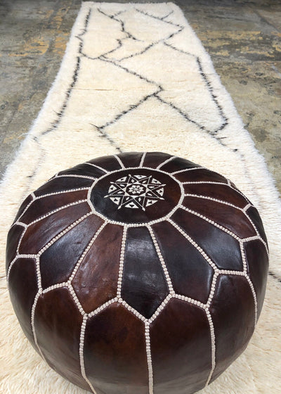dark brown leather floor cushion Moroccan leather pouf on a white soft beni ourain runner rug