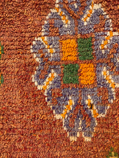 handwoven colorful design on burnt orange ottoman