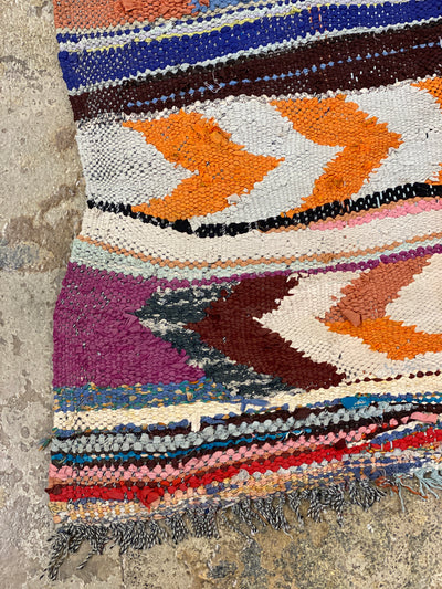 corner of handmade vintage rug with colorful stripes and arrow shapes