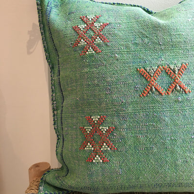 green and blue square pillow with red geometric design
