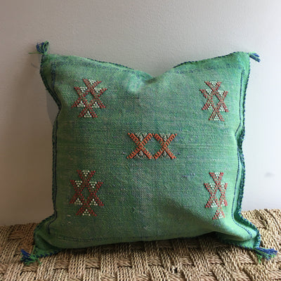 square green sabra pillow with white and red geometrical designs