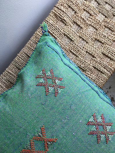 green and blue pillow with red geometric design