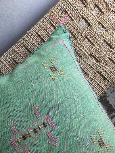 corner of green sabra pillow with pink and yellow design