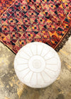 Vintage Beni Mguild Moroccan rug with red tones and a white leather pouf