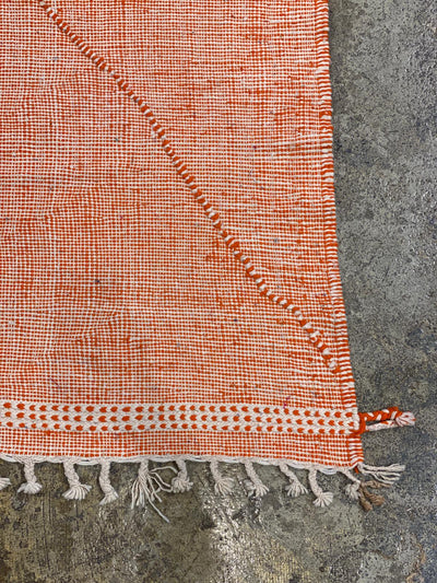 corner of orange kilim tassel rug