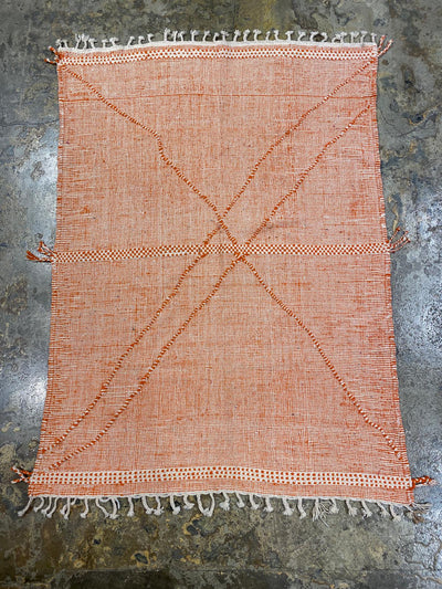 orange moroccan kilim carpet with abstract lines and white tassels