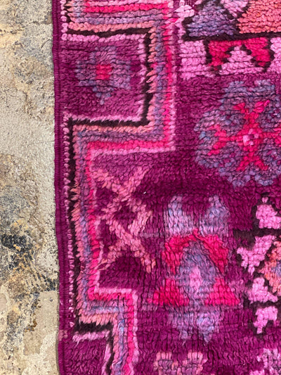 close up on colorful wool designs on vintage purple carpet