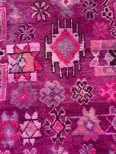 black, pink, purple and orange flower and tribal designs on purple rug
