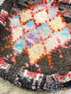 black bohemian floor cushion with colorful diamond patterns