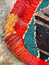 corner of moroccan floor pillow with red and colorful boucherouite design