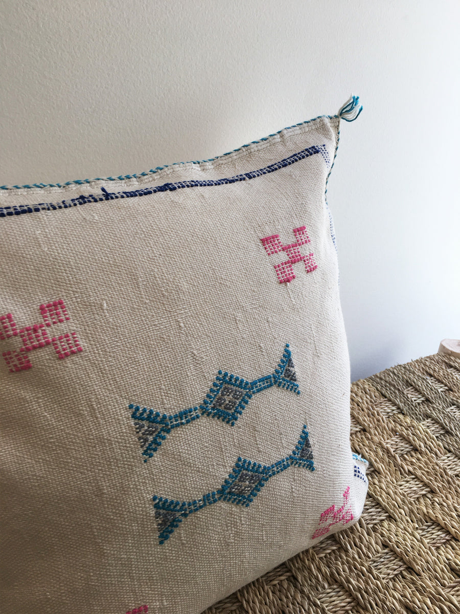 white square pillow with blue and red moroccan design